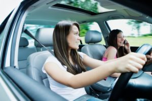 Two teenage girls (12-16) driving in car, one girl with mobile phone